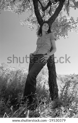 The girl in the field leans against a tree. Monochrome