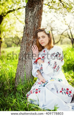 The girl in the flowered garden. Spring morning in a beautiful garden. A girl sitting on the ground. Ukrainian girl.