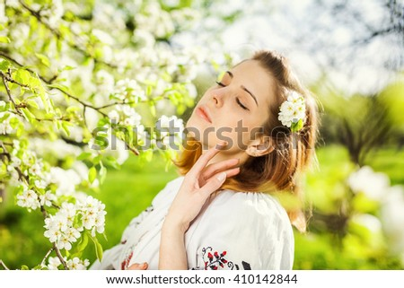 The girl in the flowered garden. Spring morning in a beautiful garden. Ukrainian girl