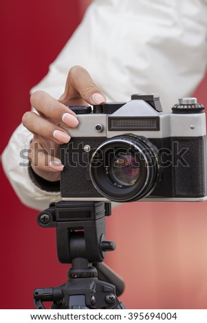 the girl in the hands of is holding the vintage camera