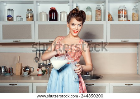 The girl in the kitchen holding a pitcher from which pours milk into a glass.