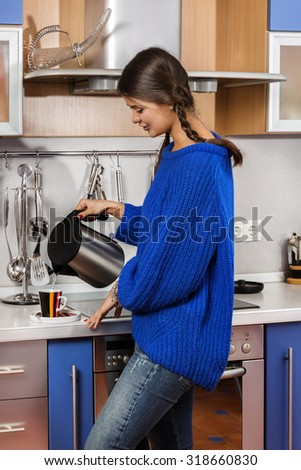 The girl in the kitchen pouring tea.