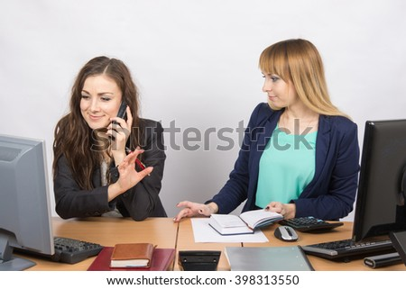 The girl in the office talking on the phone asking a colleague to wait