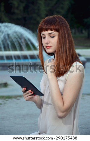 The girl in the park with tablet in hand