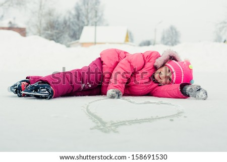 The girl in the skate on the ice drew a heart. - stock photo