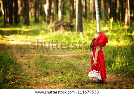 "the girl in the wood looks up.  the fairy tale "" Red Riding Hood"" - stock photo"