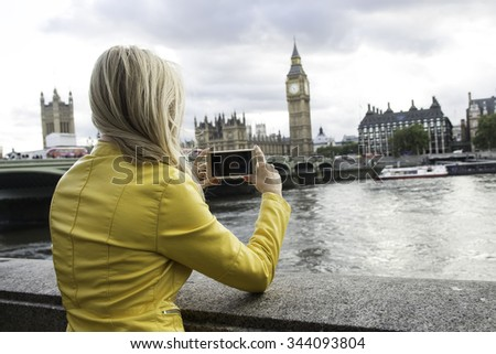 The girl in the yellow jacket, beside the River Thames pictures of Big Ben on the phone - stock photo