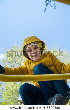 The girl in the yellow jacket climbed on arc horizontal bar on the street and looking down. bottom view - stock photo