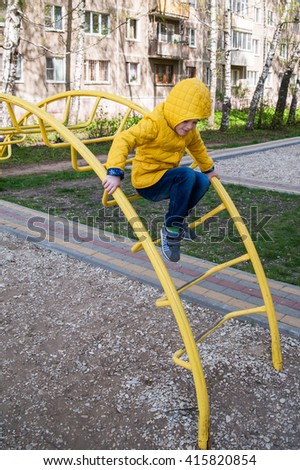 The girl in the yellow jacket sitting at the bar with an arc rungs on the street and looking down - stock photo