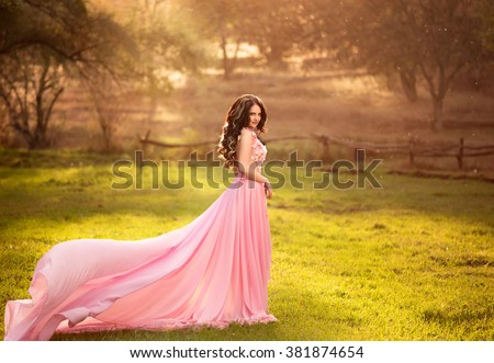 The girl in transparent pink dress with a long train flying,  fairytale princess stands on top of the green hills, creative computer  color  fashionable toning