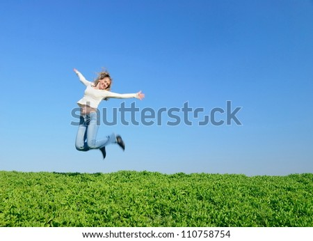 The girl in white jumps in the field - stock photo