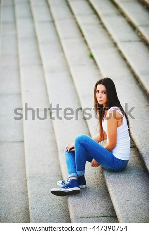 The girl in white tank top and blue jeans sitting on the stairs and looks up.
