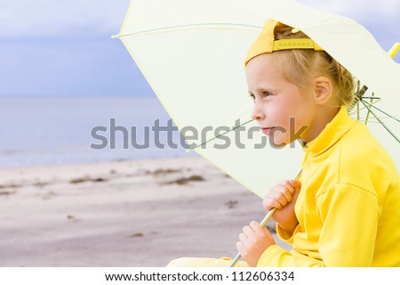 The girl in yellow clothes with umbrella sitting on the beach.