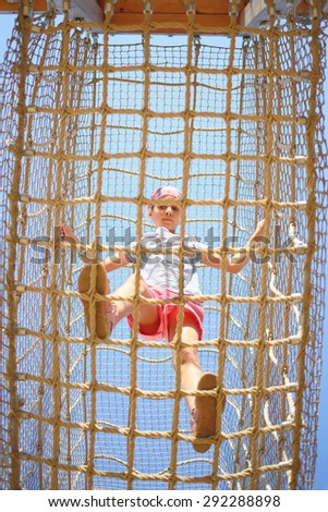 The girl inside the cable cell in playground, bottom view - stock photo