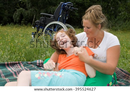 The girl is a disabled person with a helper sit on the grass.
