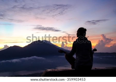 The girl is engaged in yoga and meditation in the mountains at dawn. Mountains of the island of Bali, Indonesia. Stock image.