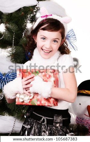 The girl is happy to receive New Year's gift, a beautiful Christmas tree