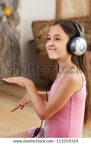 The girl is listening to music and dancing