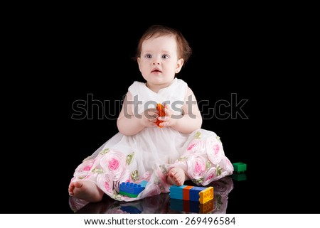 The girl is one year in dress sitting on a black background. - stock photo