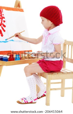The girl is painting on the easel.happy childhood, carefree childhood concept.