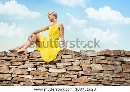 The girl is sitting on a stone wall against the blue cloudy sky - stock photo