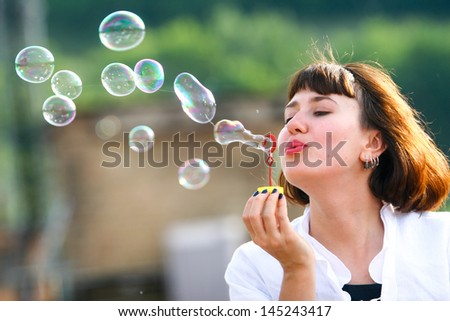 The girl is sitting on the roof of the house and blows bubbles
