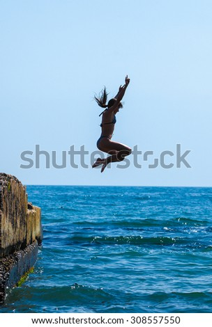 The girl jumping in the sea - stock photo