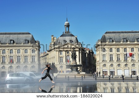 The girl jumping on water mirror of Bordeaux in French  - stock photo