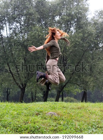 The girl jumps on a grass and trees as a background
