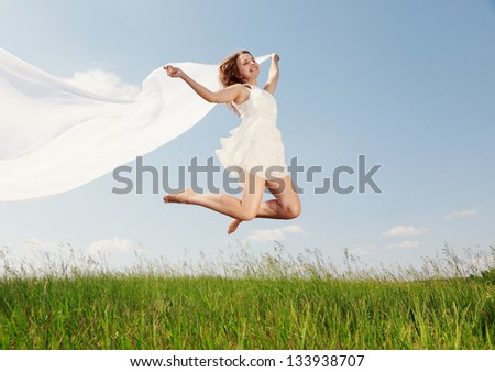 The girl jumps on a green grass