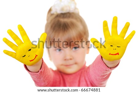 The girl keeps hands which are painted in yellow color. Isolated over white - stock photo