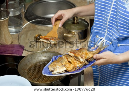The girl lays on a plate fried fish in a golden a crust.