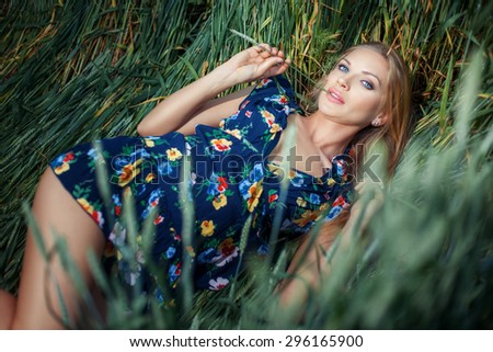 The girl lies in green grass. In the mouth, holding ears of wheat. - stock photo