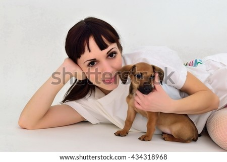 The girl lies on a white background and hugging dachshund