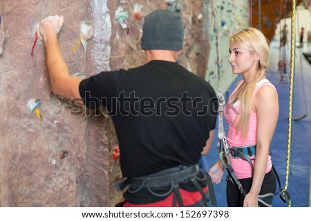 The girl listens to instructions on climbing by coach - stock photo
