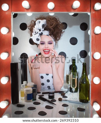 The girl looks at herself in the mirror and lipstick lipstick - stock photo