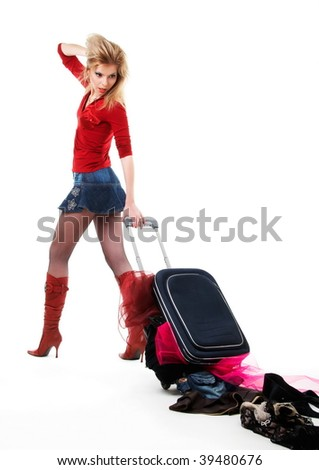 The girl looks at scattered things from a suitcase.