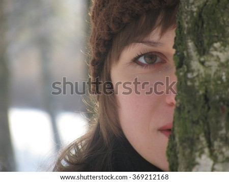 The girl looks behind a tree - stock photo