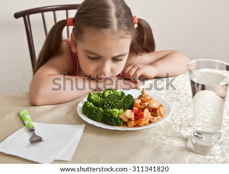 The girl looks indifferently at the dish with meat and broccoli