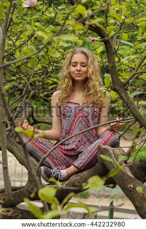 The girl meditates sitting on magnolia tree in the garden, lotus pose