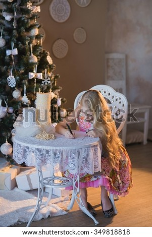 The girl near a Christmas tree with a favorite toy rabbit writes a letter to Santa, boxes, Christmas, New Year, lifestyle, holiday, vacation, waiting for santa