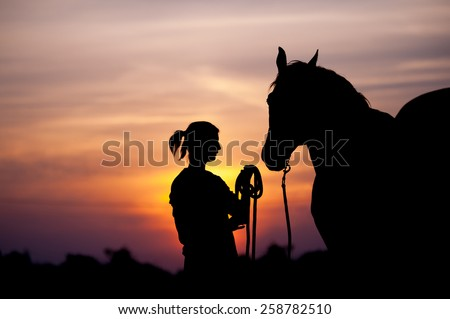 The girl near to a horse standing in front of a beautiful sunset. Silhouette of a woman and a horse. Human holding the horse by the rope.