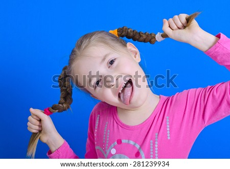 the girl of nine years has fun in studio and puts out the tongue. The photo on a blue background  - stock photo