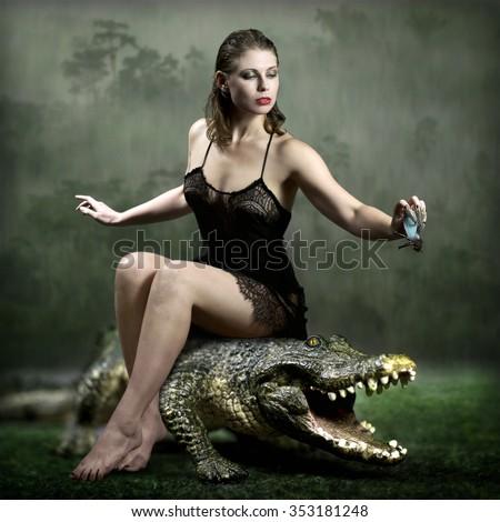 The girl on a crocodile - stock photo