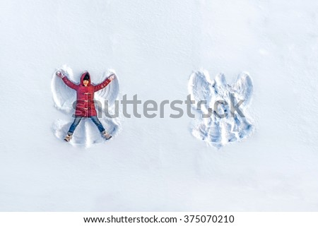 The girl on a snow angel shows - stock photo
