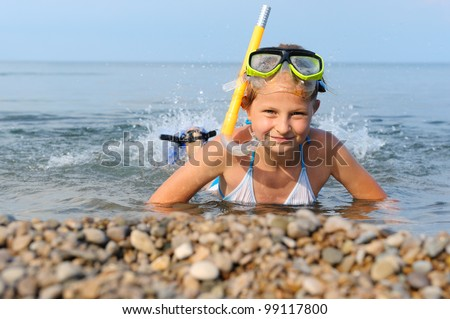 The girl on seacoast flounders about in water. In a mask, flippers and with a snorkel - stock photo