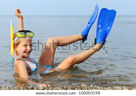 The girl on seacoast. In a mask, flippers and with a snorkel - stock photo