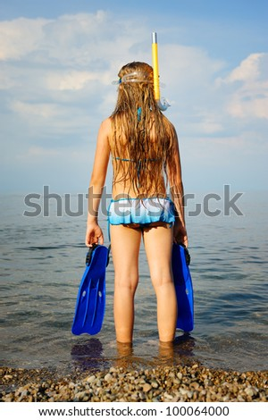 The girl on seacoast looks in a distance. In a mask, flippers and with a snorkel - stock photo