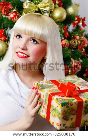 The girl on the background of Christmas tree holding a gift box in his hands