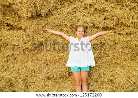 The girl on the background of the large stack of hay - stock photo